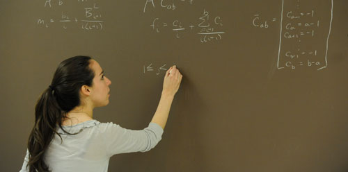 student writing equations on blackboard