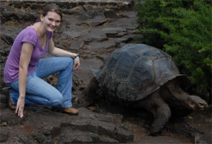Julia Stutzman poses as a tortois walk past.