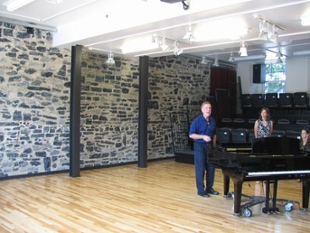 A grand piano sits on the hardwood floor in the performance area with the bluestone wall in the background.